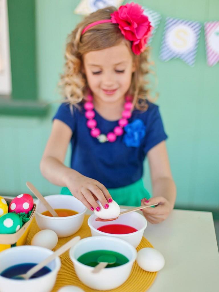 Девочка красит яйца